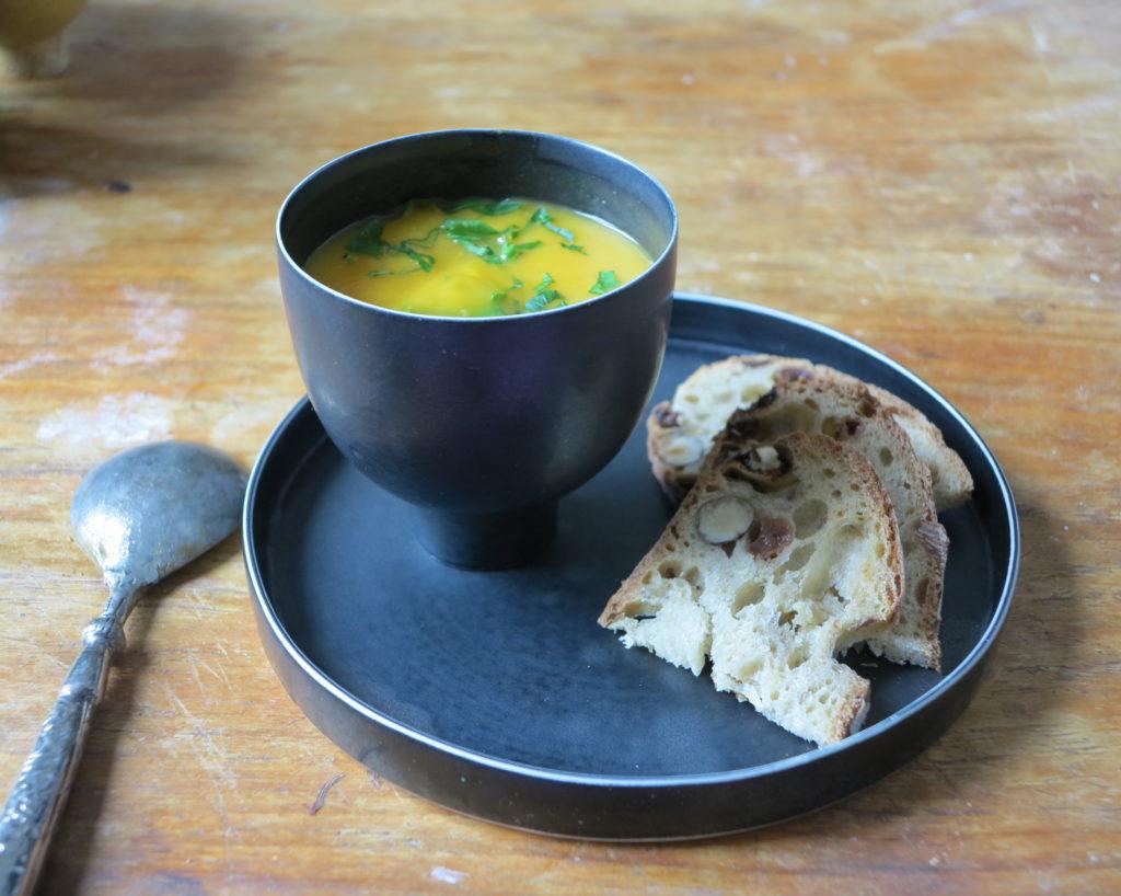 Bol et assiette de la créatrice mis en scène avec une soupe et 2 tranches de pain